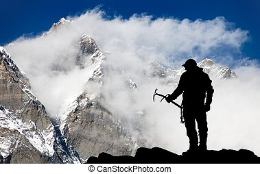 Mount Lhotse and silhouette of man wirh ice axe - trek to...