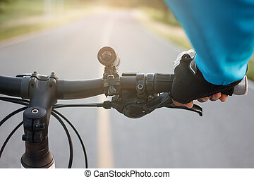 Hands in gloves holding handlebar of a bicycle on road.