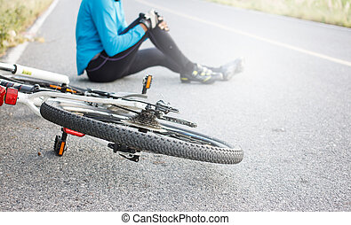 cyclist fell down from bike with injured knee joint sitting...