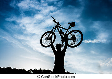 biker is holding bicycle above his head at sunrise.