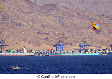 Parasailing in Eilat, Israel against port of Aqaba Jordan -...