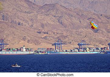 Parasailing in Eilat, Israel against port of Aqaba Jordan -...
