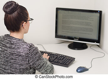 woman typing behind computer
