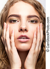 Portrait of beautiful young girl with hands on the face.
