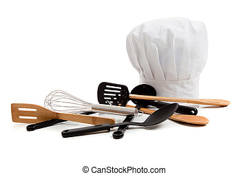 Chefs toque with various cooking utensils on white - A white...