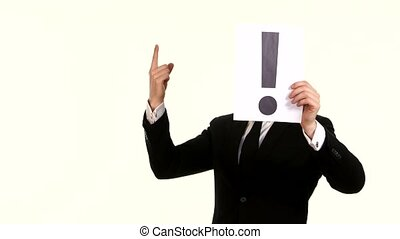 young businessman holding a sheet with exclamation mark on...