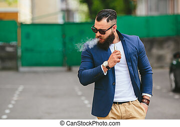 well-dressed man smoking electronic cigarette - man with a...