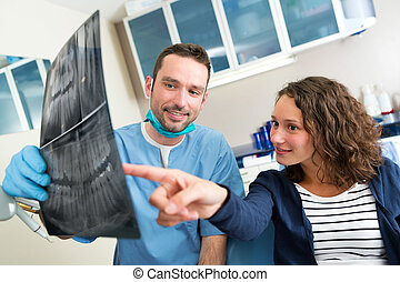 Young attractive dentist showing x-ray to patient