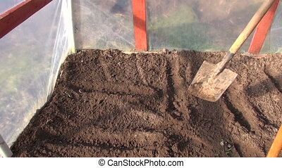 gardener in spring rake soil in plastic greenhouse