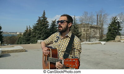 Brutal man with a beard wearing glasses walking down the street and plays guitar