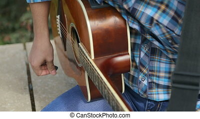Close up of a talented guy in the blue plaid shirt playing guitar on the street