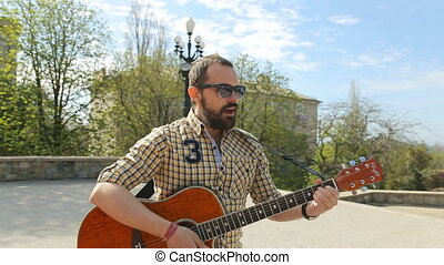 Handsome guy with a beard wearing glasses walking down the street and playing guitar