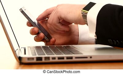 Businessman using his smart phone and laptop on white
