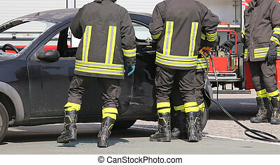 firefighters in action during the car accident -...