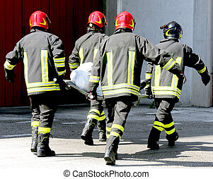 firemen in action carry a stretcher with injured -...
