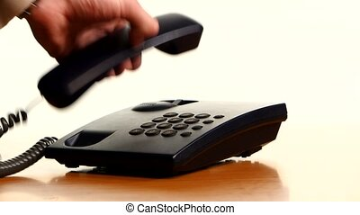 Businessman making a phone call on landline telephone...