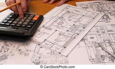 Developing engineering project. Male architect checking numbers on blueprint during house construction planing. Slow motion