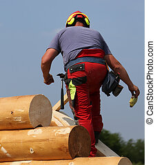 Carpenter with helmet and protective equipment on the roof of the House