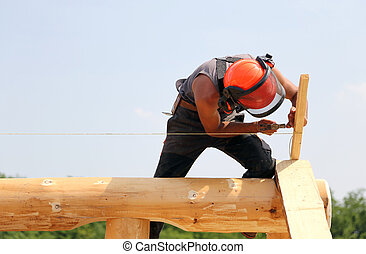 Carpenter with helmet and protective equipment to work safely on the roof