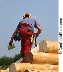 Carpenter with helmet and protective equipment to work safely on the roof of the House