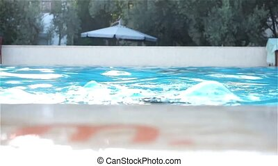 Teenage boy swimming in pool - Young teenage boy swims and...