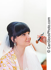 Makeup bride brunette in a dressing gown sits