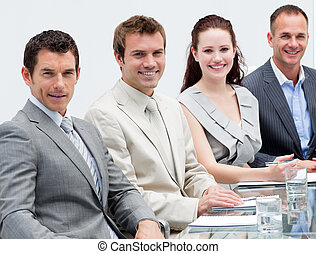 Close-up of smiling business people sitting in a meeting