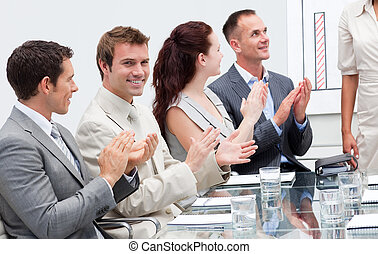 Smiling business people applauding a colleague after giving...