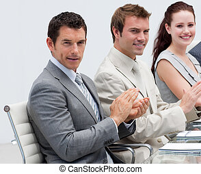 Attractive businessman applauding in a meeting