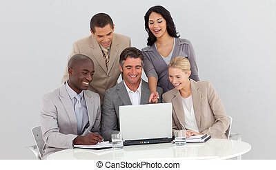 Multi-ethnic business team studying sales figures in the...