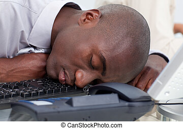Afro-American businessman sleeping on the keyboard