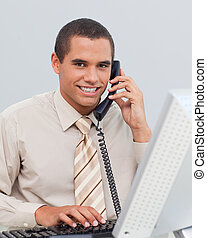 Young businessman talking on phone in the office