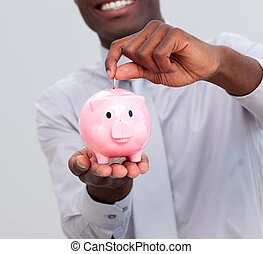 Afro-American businessman saving money in a piggybank in the...