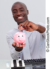 Happy Afro-American businessman saving money in a piggybank...