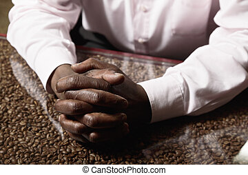 Clasped hands on tabletop - Clasped hands of a man on...