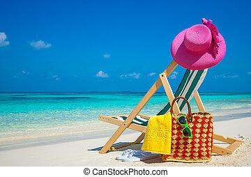 Beach chairs on the white sand beach with cloudy blue sky...
