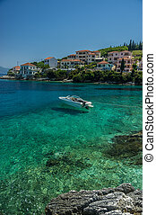 Speedboat moored in turquiose bay in Kephalonia with houses...