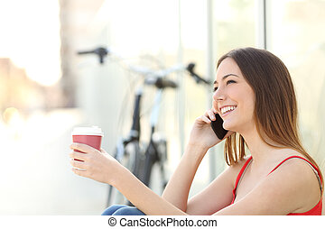 Girl calling on the mobile phone and drinking coffee sitting...