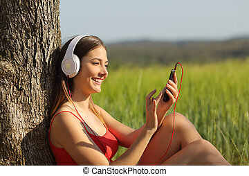 Girl listening to the music and downloading songs in a field...