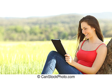 Relaxed woman reading an ebook in the country leaning under...