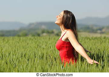 Woman breathing fresh air in a meadow and touching the wheat...