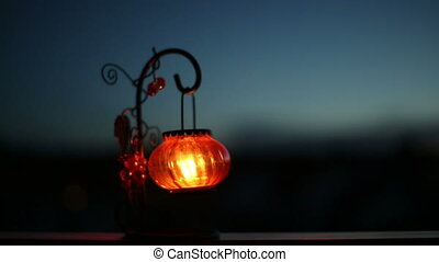Lantern with a candle swaying in the wind at night