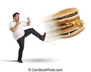 Kick  to calories - Fat man kicks a giant fat sandwich