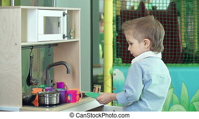 At the Fun Centre - Boy finishing playing with mini kitchen
