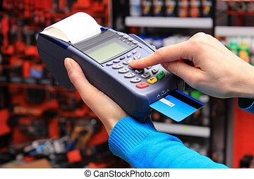 Paying with credit card in an electrical shop, finance...