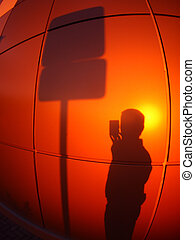 The silhouette of a man on a red-orange wall, who...
