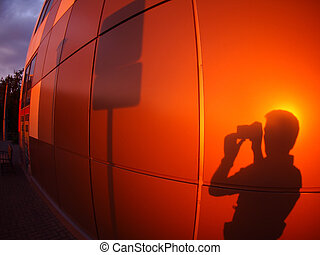 The shadow of a man on a red-orange wall, who photographs a...