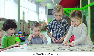 Tabletop Game - Close up of four kids playing with...