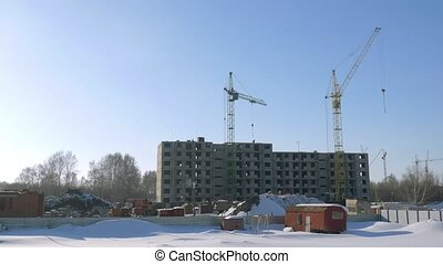 Crane on the construction site with workers by winter. HD