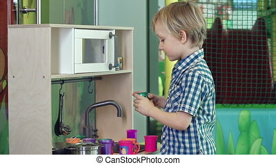Toy Kitchen Set - Side view of little boy cooking in play...